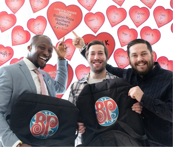 Kyle and Neil MacPherson pose at the Heart Pledge Day 2019 Heart Wall with UHF staff.